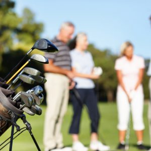 Focus on golf kit with friends standing on golf course and discussing